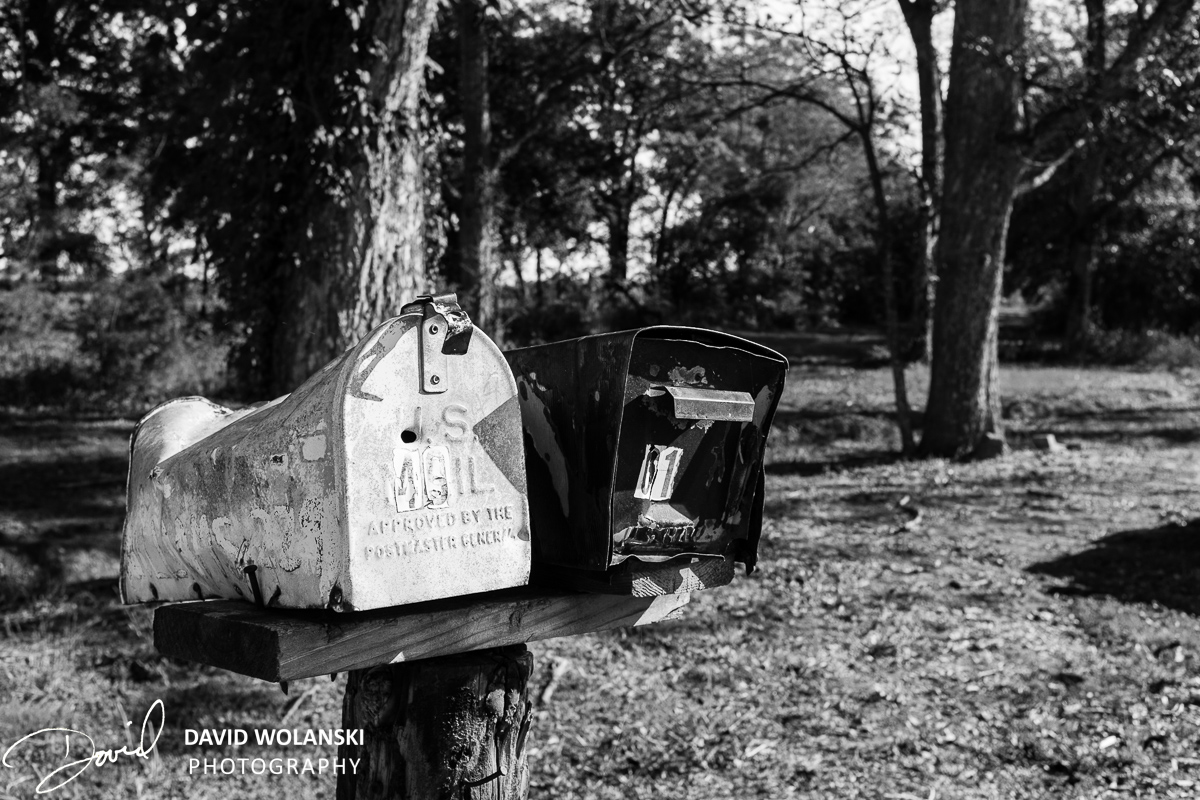 Black and white mail boxes, one with bullet hole