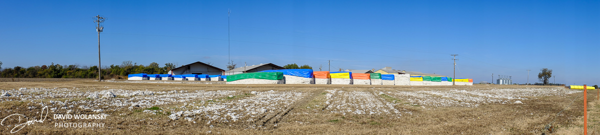 Bales of Cotton with colored plastic covers at a Gin awaiting processing