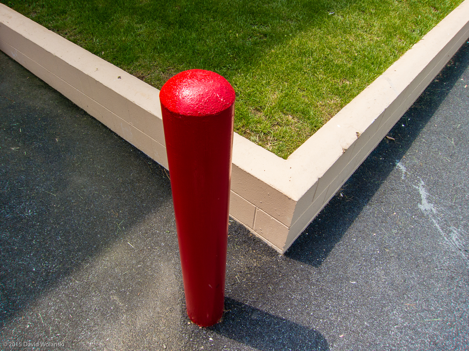 Red Post, Green Grass and Black Pavement