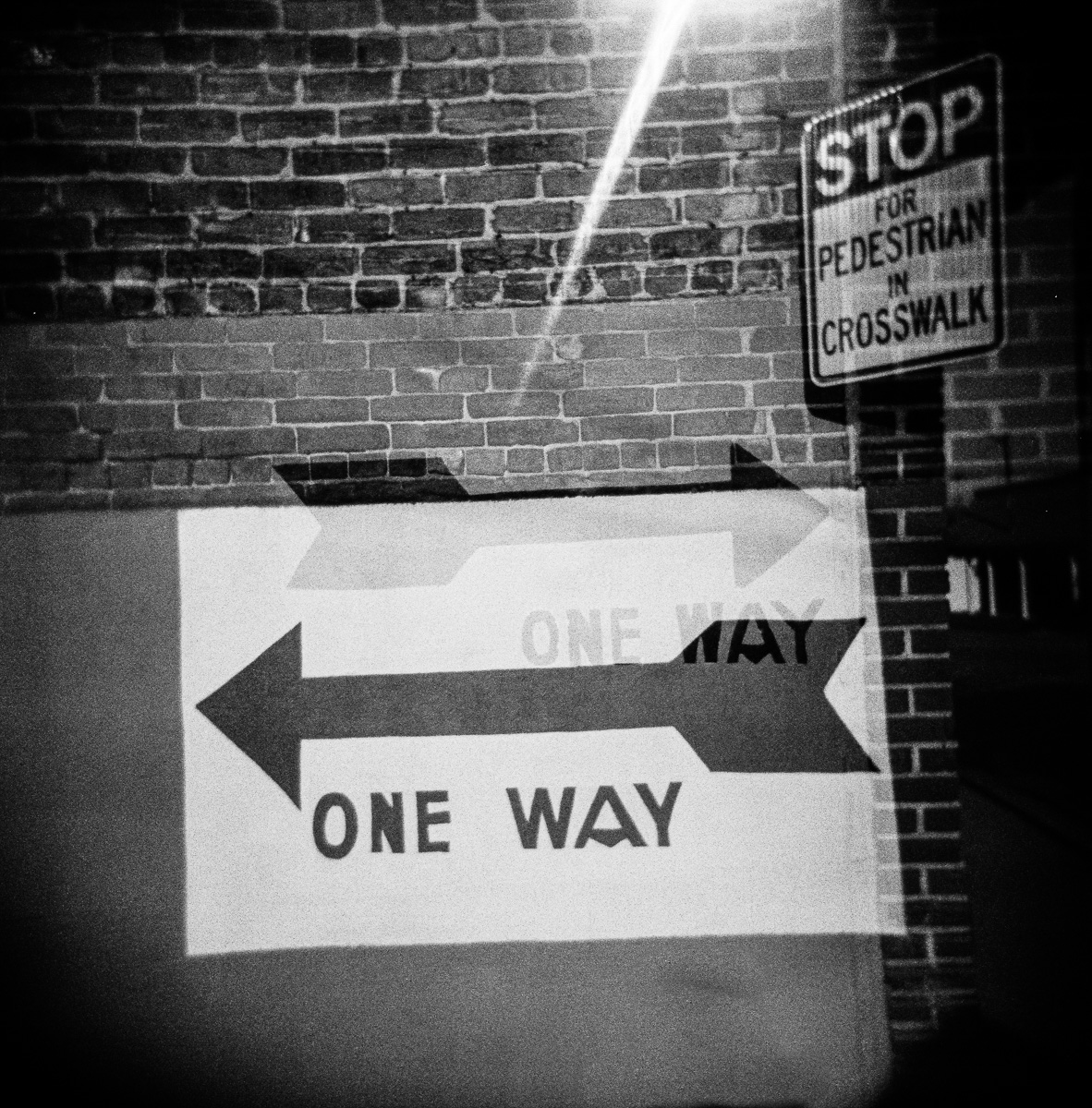 Double Exposure of two one way signs going in opposite directions.